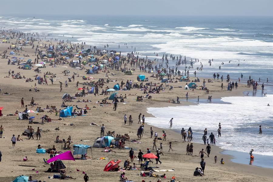 本周末4日為美國國慶日,專家警告美國當前疫情仍在攀升,許多仍過早開放的地方恐會有大量遊客湧入,在疫情未降溫下,將形成「完美風暴」。圖為5月陣亡將士紀念日時,舊金山海灘湧入大批人潮。(美聯社)