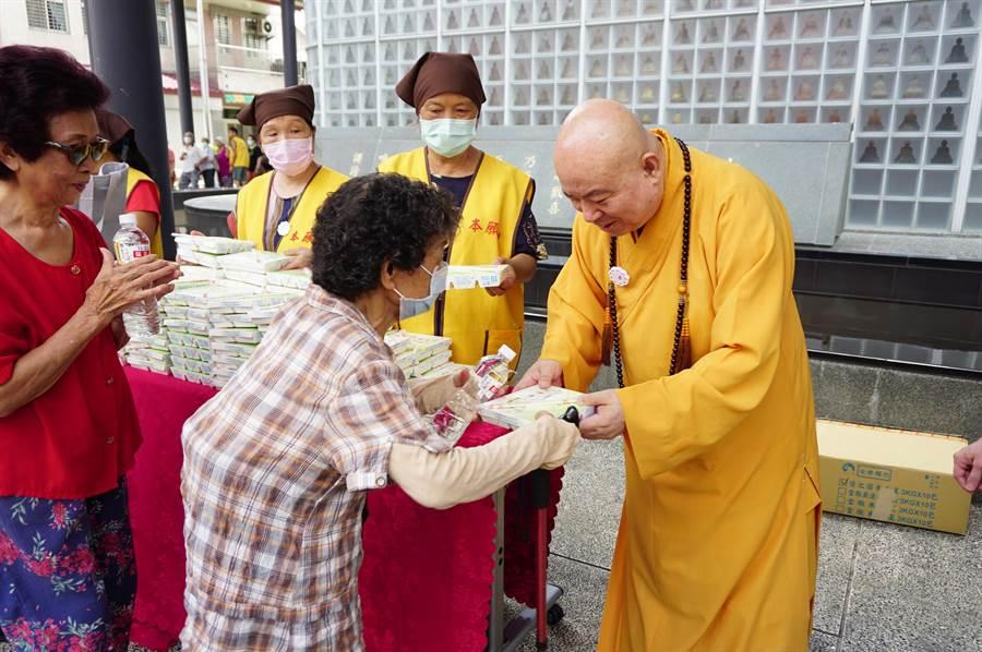 本願山住持信願法師(右)推廣「茹素即放生」,發起「彌陀齋」活動,每天發送100個素餐盒。(王文吉攝)