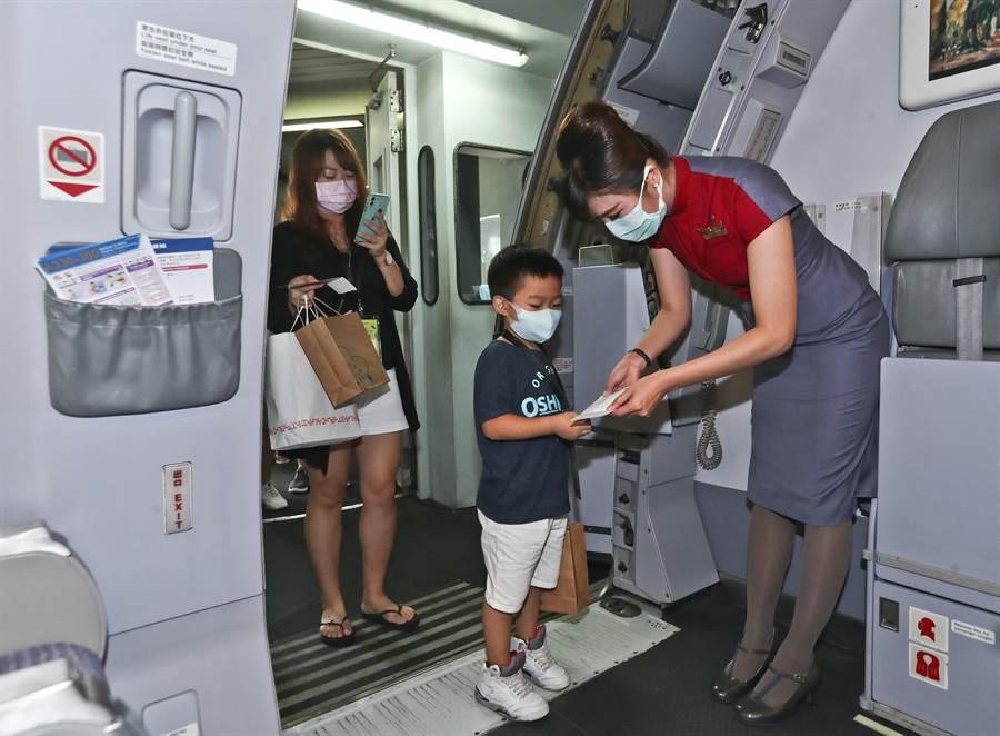松山機場2日舉辦「偽出國體驗」活動,參加民眾在華航空姐查驗登機證後,依序登機。(劉宗龍攝)