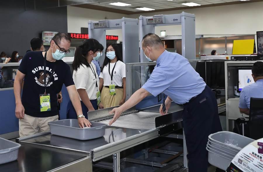 松山機場2日舉辦「偽出國體驗」活動,參加民眾依序通過金屬偵測門,並配合航警人員完成隨身物品安檢。(劉宗龍攝)