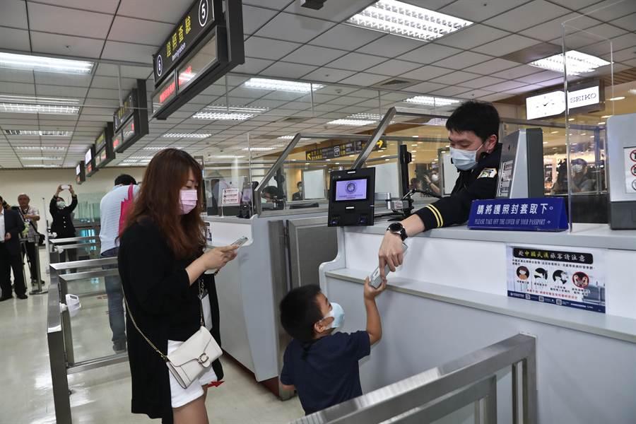 松山機場2日舉辦「偽出國體驗」活動,參加民眾在證照查驗櫃檯接受移民官查驗證照核對身分。(劉宗龍攝)
