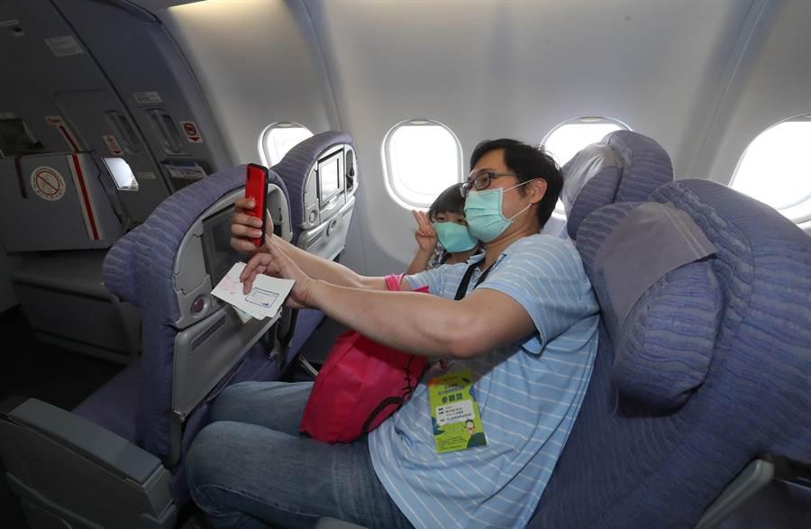 松山機場2日舉辦「偽出國體驗」活動,參加活動的一對父女開心在華航機艙內合影。(劉宗龍攝)