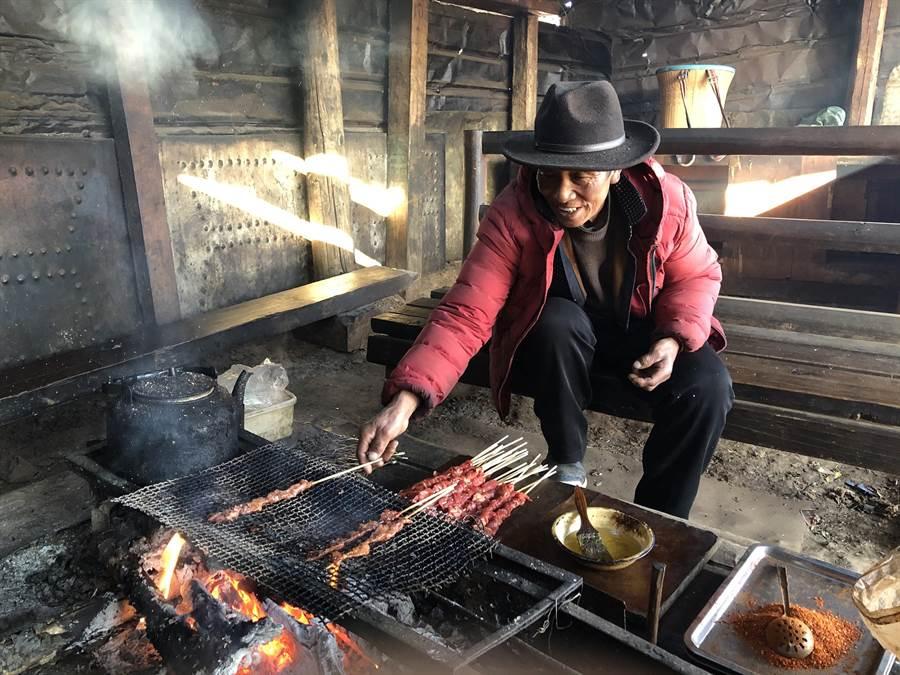 雪山上烤犛牛肉的藏族老阿爸。(作者提供)