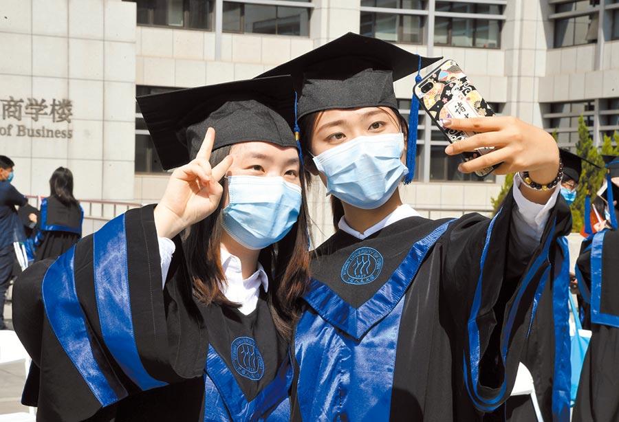 6月30日,中國人民大學畢業生在畢業典禮結束後,戴著口罩合影。(新華社)