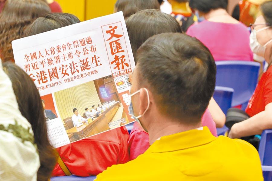 7月1日,港民在閱讀報紙上有關《香港國安法》生效的新聞。(中新社)