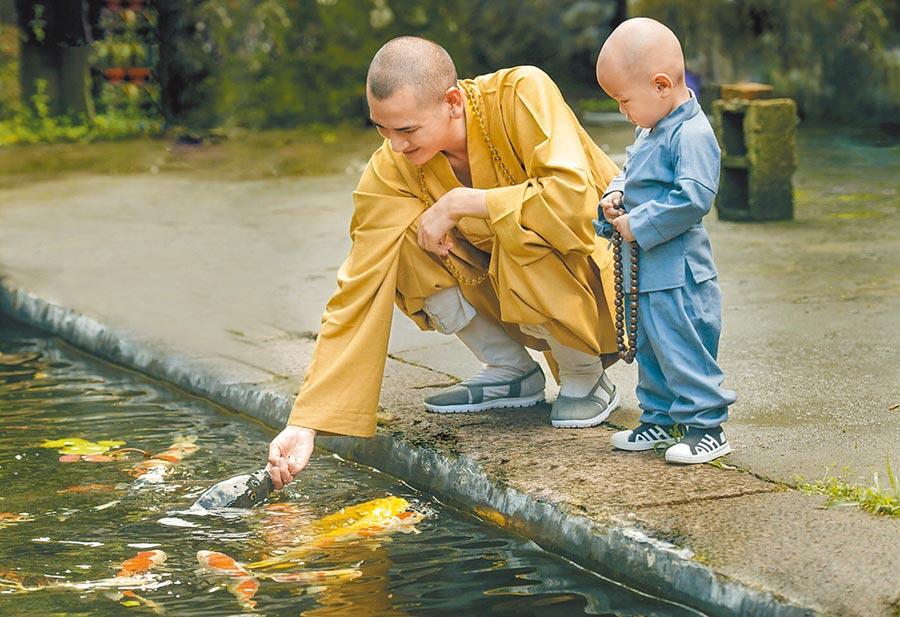 釋明心與一名打扮成小和尚的孩子一同餵魚。(取自新浪微博@釋明心)