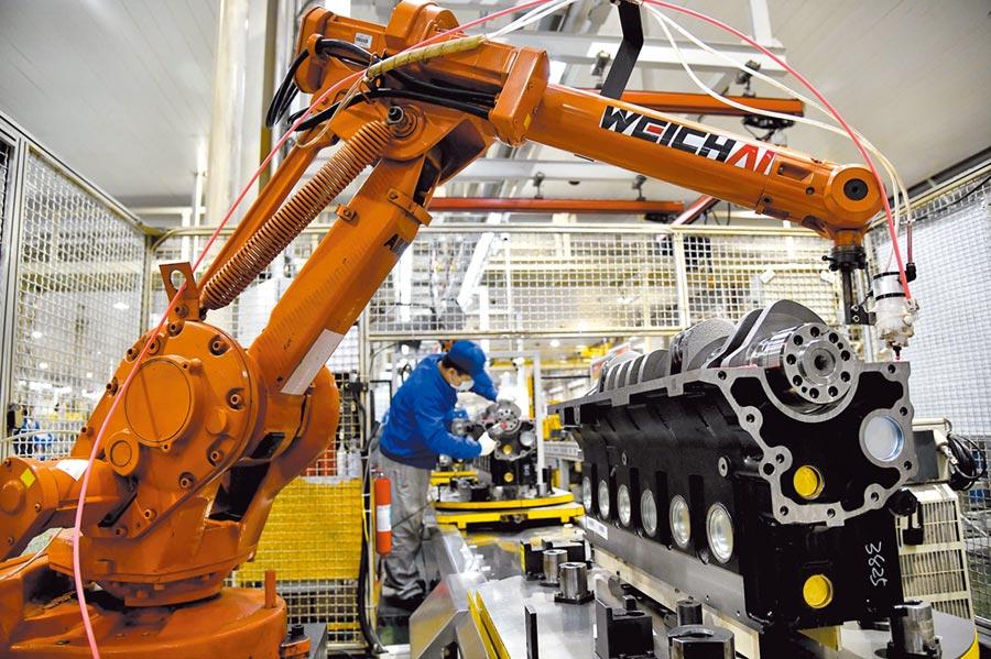 6月財新中國製造業PMI為51.2,創今年最高。圖為山東濰坊一工廠生產線,工人們在裝配發動機。(新華社)