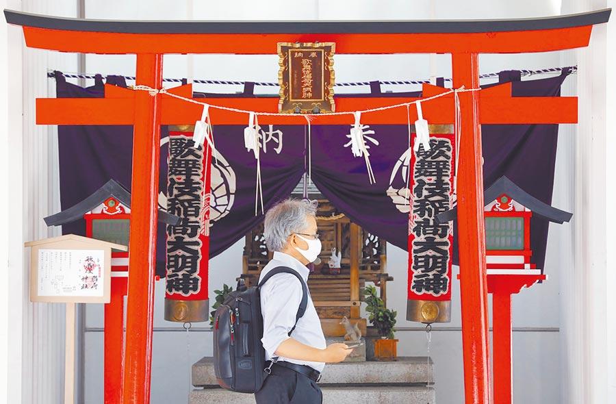 東京單日確診數破百,新冠疫情又拉警報。圖為民眾戴著防護口罩走過神社的鳥居門。(路透)