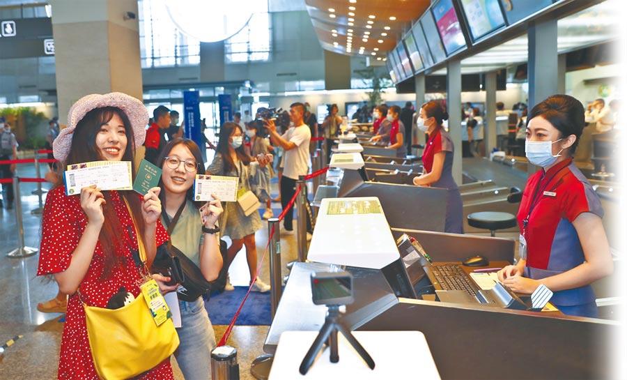 松山機場2日舉辦「偽出國體驗」活動,參加民眾在機場櫃檯報到,領取登機證後,開心展示登機證,過過乾癮。(劉宗龍攝)