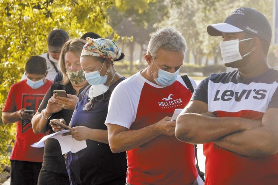 國慶假期前夕,全美新增確診超過5.2萬,再度刷新單日新高紀錄。佛羅里達州和德州2大重疫區,一周內確診總和甚至超過歐洲27國。圖為佛州一家商場外,民眾戴口罩排隊進入。(美聯社)