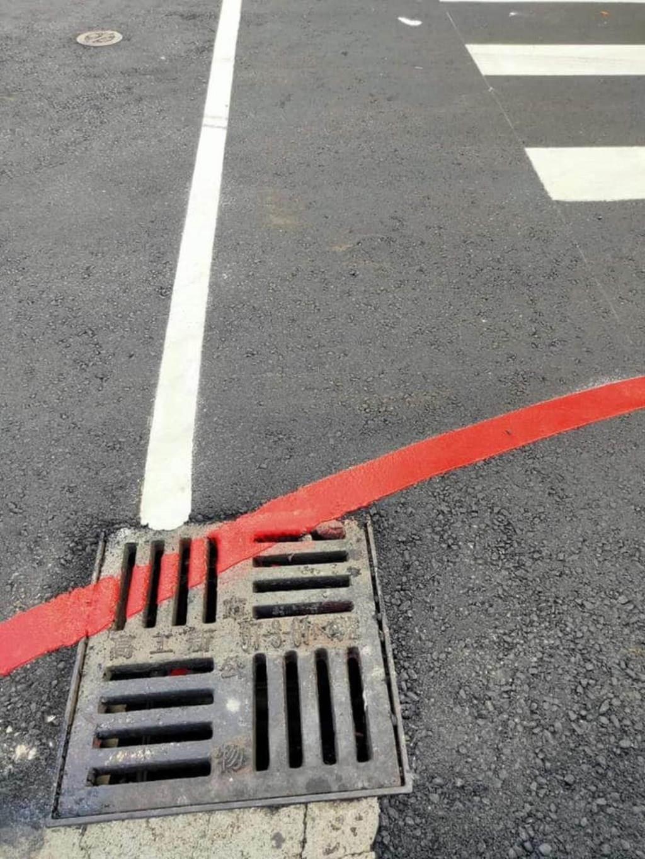 網友加碼上傳了一張奇葩照,自強二路、前金一街口也有一處紅線劃過水溝蓋。(翻攝「韓黑父母不崩潰」粉專)