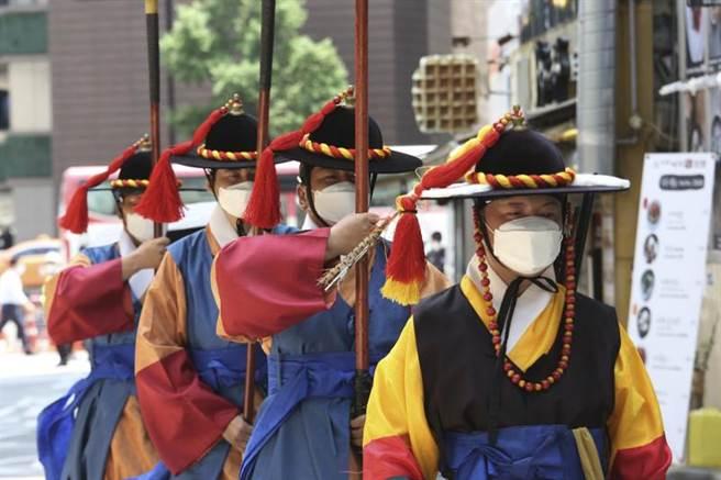 南韓首爾疫情仍未平息。圖為首爾穿傳統服裝的皇宮守衛戴口罩。(美聯社)