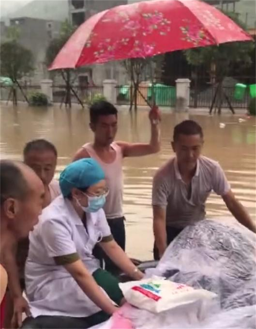 雲南產婦轉移時由醫生與巡邏隊員協助,以輪胎加擔架運送通過洪水,卻在飄浮輪胎上完成分娩。(圖/央視截圖)