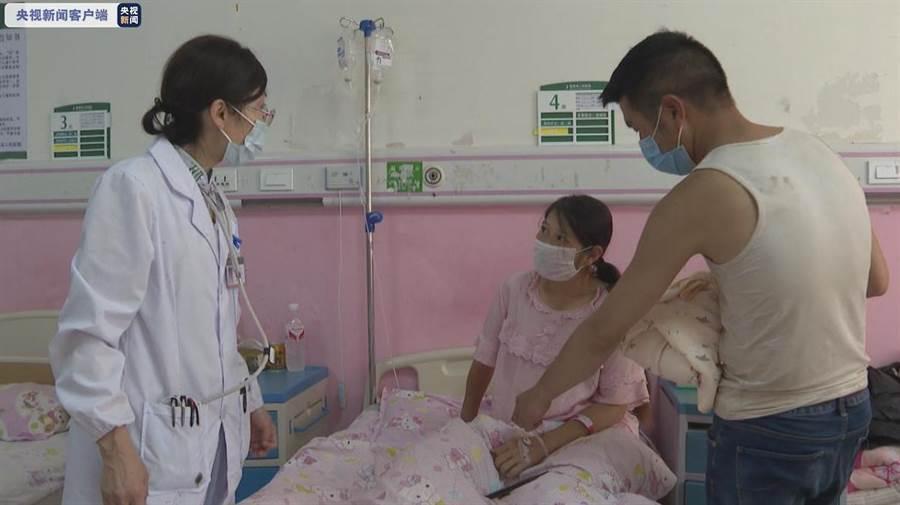 產婦在飄浮輪胎上分娩後,終於上了救護車送往縣城醫院,經治療後母子平安。(圖/央視截圖)