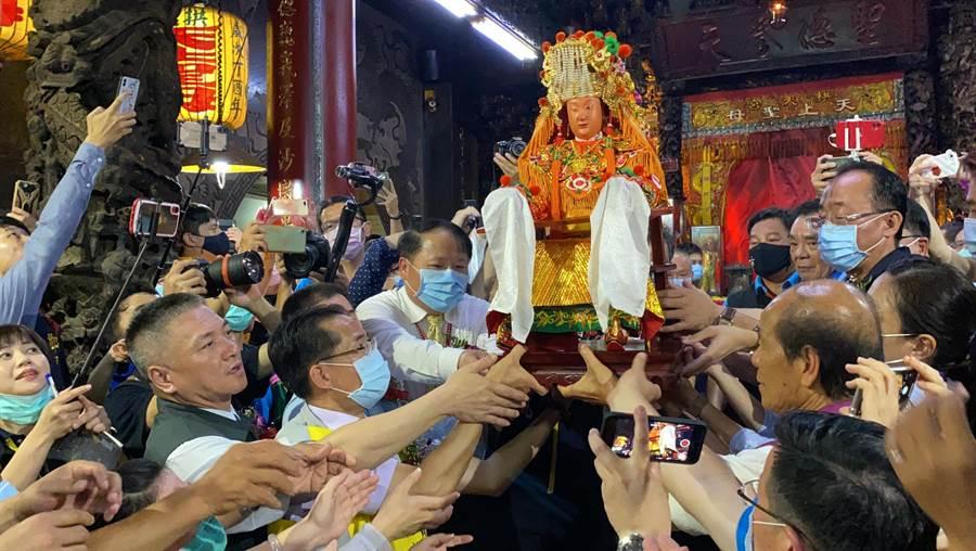 白沙屯媽祖神像由眾人以人力接駁方式接上神轎安座。(巫靜婷攝)
