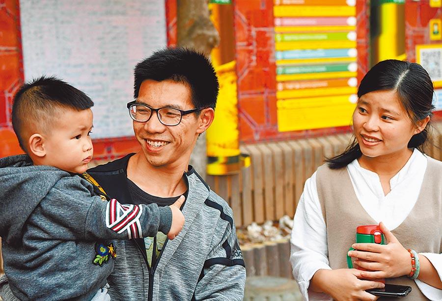 受新冠疫情影響,兩岸新婚夫妻(「小紅」)團聚入境全面暫緩,造成夫妻分隔兩地。圖為台灣青年洪超雄和晉江姑娘施清雅帶著小孩在村內遊玩。(中新社)