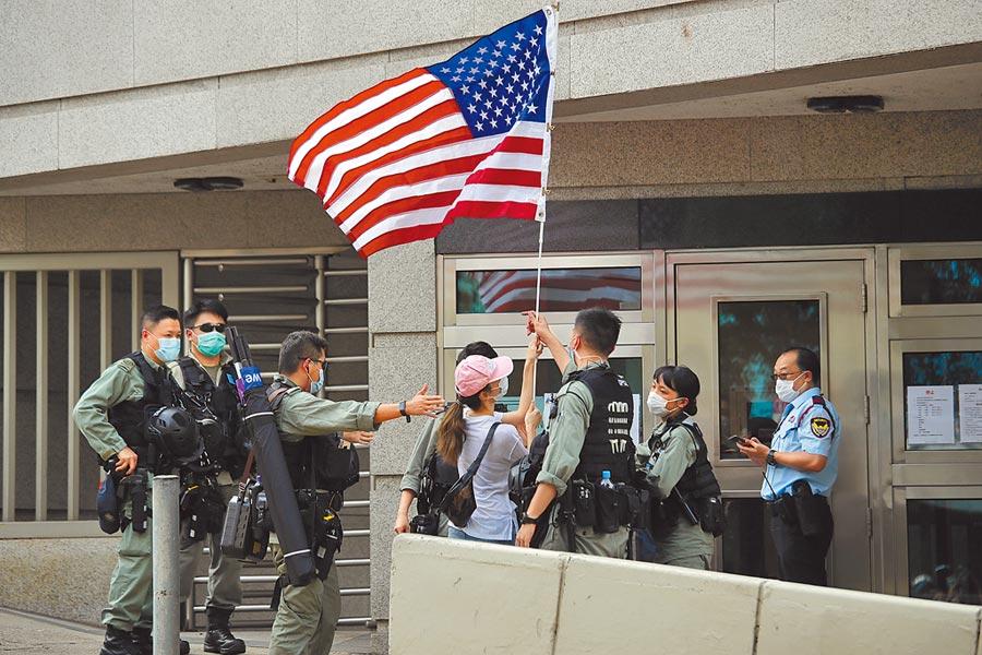 一名香港女性抗議者不滿《香港國安法》通過實施,趁著昨天帶著美國國旗上街,結果在美國總領事館前遭鎮暴警察團團包圍。(美聯社)