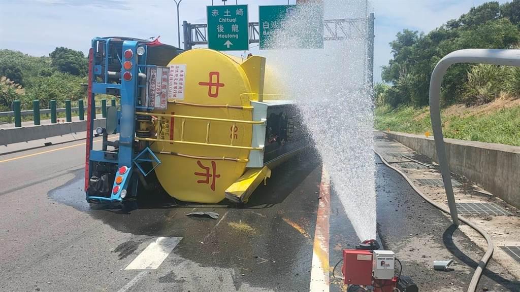 載運23噸鹽酸溶液的大型槽車不慎翻覆,造成槽內液體外洩,消防隊員趕緊灑水稀釋降溫。(民眾提供/何冠嫻苗栗傳真)