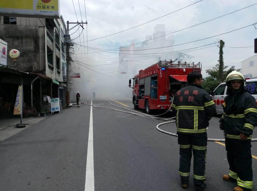 雲林縣虎尾早餐店火警,濃煙幾乎淹沒道路,消防隊灌救。(許素惠攝)