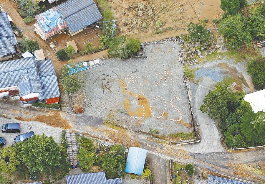 日本媒体的直升机5日拍到,熊本县的受灾居民在地上排出「食、米、水」与「SOS」等求救字样,希望早日获救。(路透)
