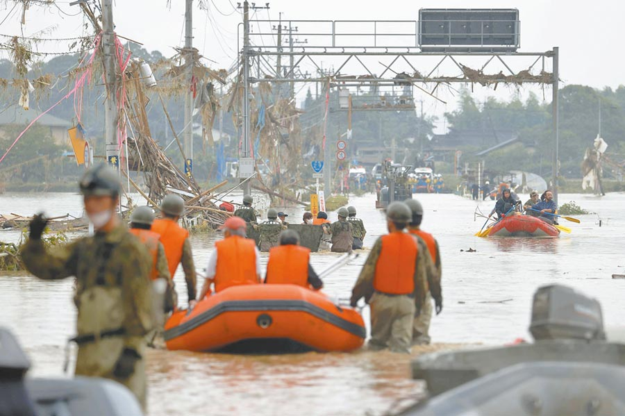 日本政府5日动员1万名自卫队员,紧急赶往熊本县灾区,用橡皮艇援救受困居民。(路透)
