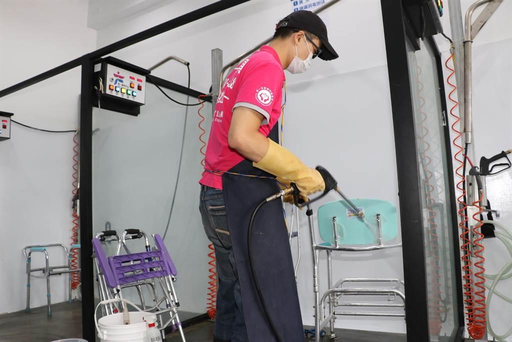 工作人員使用高壓噴槍清洗回收的二手輔具。(許哲瑗攝)