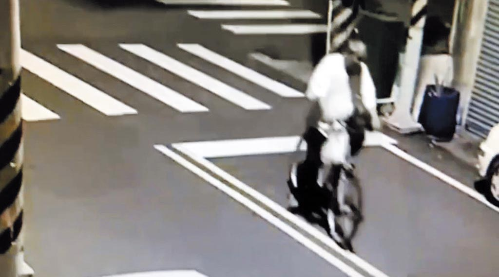 疑涉關廟惡火案的張姓男子,於火警發生數分鐘前,騎腳踏車徘徊現場,手把上還提著1袋物品,但再次出現時,物品已消失。(民眾提供/李宜杰台南傳真)
