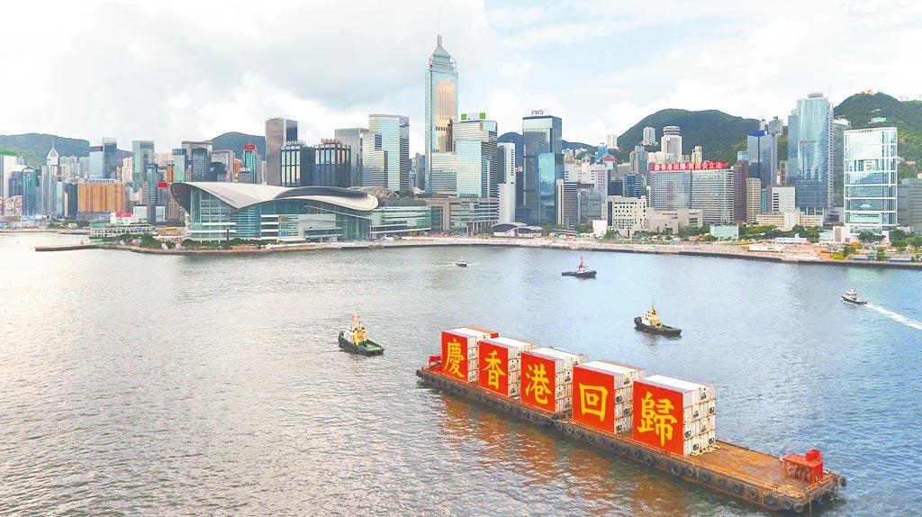 7月1日,載著「慶香港回歸」標語的船隻從香港維多利亞港駛過。(新華社)