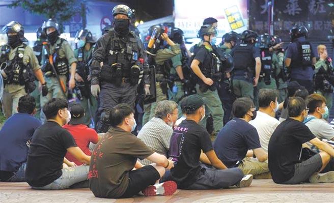 《港区国安法》实施首日有香港网民发动游行,港警下午对游行举旗警告,至晚上8时,已拘捕超过300人,当中9人(5男4女)以涉嫌违反香港《国安法》被捕。(美联社)