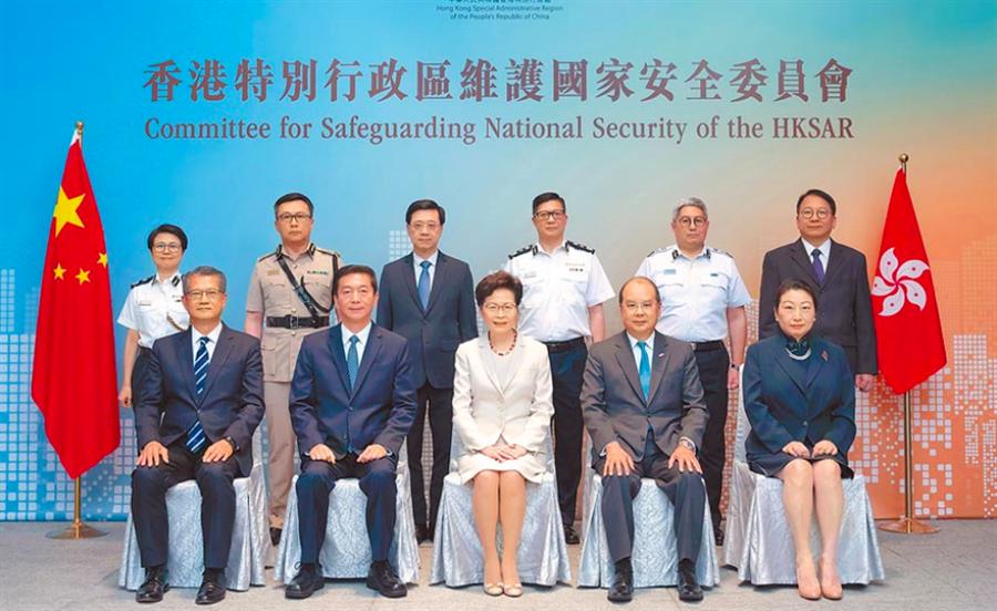 香港國安委昨日舉行首次會議,主席林鄭月娥(前排中)、與國安委顧問駱惠寧皆(左二)出席會議。(路透)