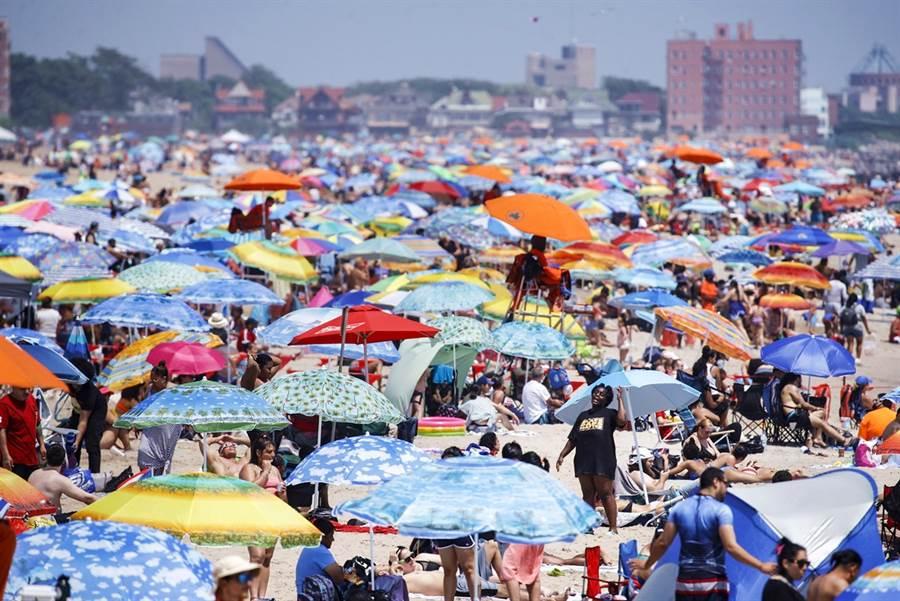 由於過早解封,加上民眾報復性出遊,美國新冠肺炎疫情持續惡化,32個州感染率攀升,各地重現大批民眾湧入醫院畫面,遭專家形容美國疫情正處於「自由落體」狀態。圖為4日美國獨立日當天,紐約市科尼島(Coney Island)海灘景象。(圖/美聯社)