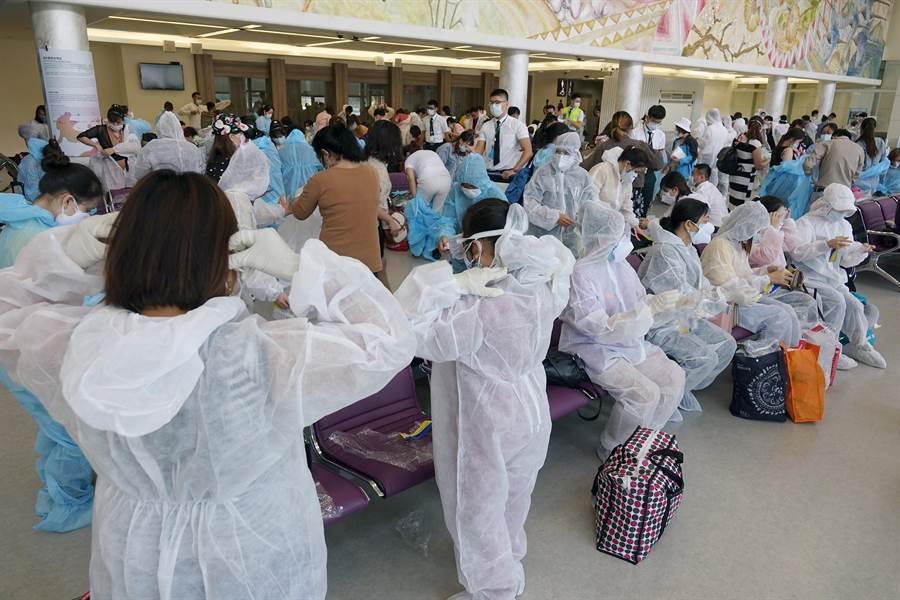 由越南政府與越捷航空公司合作的撤僑專機,7日中午來台搭載240名越籍旅客回胡志明市,旅客穿上航空公司發給的防護衣、口罩、眼罩及手套,在候機室等候登機。(陳麒全攝)