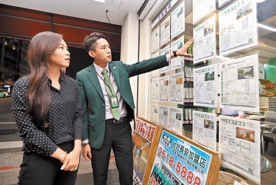 外貿協會董事長黃志芳昨日指出,疫情不會那麼快過去,日本所謂「低體溫經濟」,低成長、低通膨、低利率等「三低」將成新常態。圖為房仲從業人員細心地向客戶介紹物件。(本報資料照片)