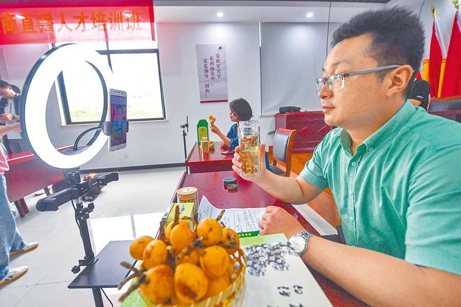 通過考核直播薪資高,條件十分誘人。圖為杭州枇杷果農當主播,推銷特色農產品網售。(新華社)