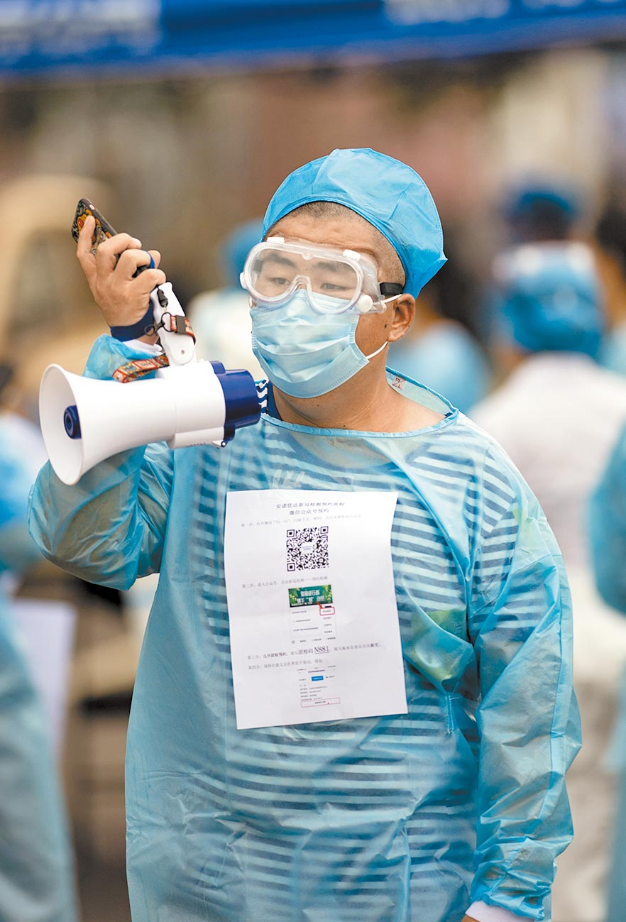 6月26日,北京豐台新冠肺炎核酸檢測採樣點,社區志工將二維碼和填寫指南等資訊貼在身上,方便市民登記。(中新社)