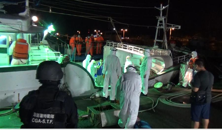 海巡署偵防分署查獲「瑞蓬成2號」漁船接駁30名越南籍偷渡客企圖闖關入境,專案小組穿著全套防護衣、口罩等防疫裝備登船檢查。(海巡署提供/王文吉台中傳真)