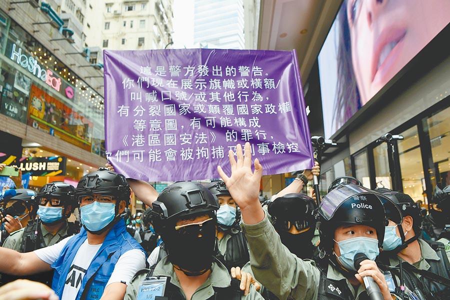 香港國安法實施細則點名台灣,形同侵犯我管轄權,蔡英文總統表示,不排除祭出反制措施。圖為香港國安法實施後,警方首次舉起紫旗警告。(中新社)