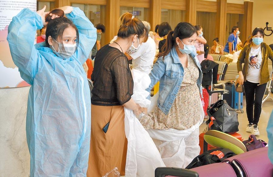 由越南政府與越捷航空公司合作的撤僑專機,7日中午來台搭載240名越籍旅客回胡志明市,旅客穿上航空公司發給的防護衣、口罩、眼罩及手套,才能上飛機。(陳麒全攝)