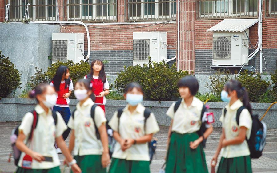 教育部長潘文忠7日宣布,全國中小學2年內全面裝設冷氣,總經費約新台幣323億元,中央會補助其中9成。圖為一群國中學生放學後,走過教室外的冷氣機前方。(范揚光攝)