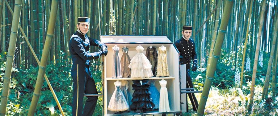 DIOR高訂服短片中,門僮扛著大箱子步入山林,向森林仙子展示37件縮小版的DIOR高訂服,讓仙子動了凡心。(DIOR提供)