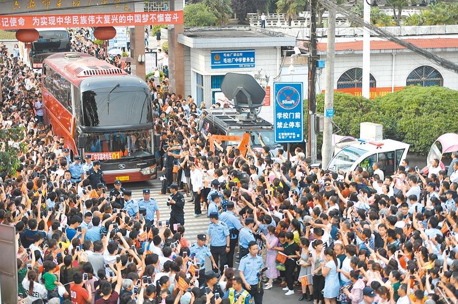 2018年6月5日,安徽「高考小鎮」送考,巴士緩緩從毛坦廠中學校門駛出,民眾夾道歡送。(中新社)