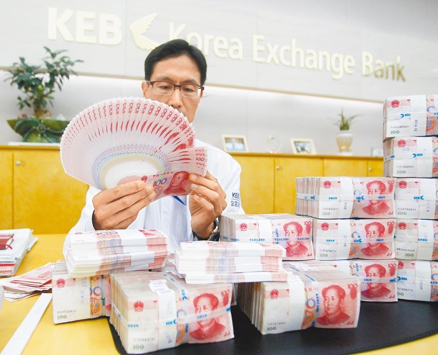 中國工商銀行首爾分行員工向記者展示人民幣業務流程。(新華社資料照片)