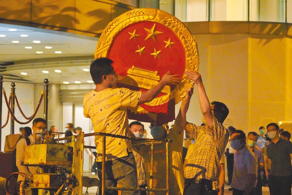 工作人員在香港銅鑼灣維景酒店外牆安裝中華人民共和國國徽。7月8日上午,中央人民政府駐香港特別行政區維護國家安全公署在這裡舉行揭牌儀式。(中新社)