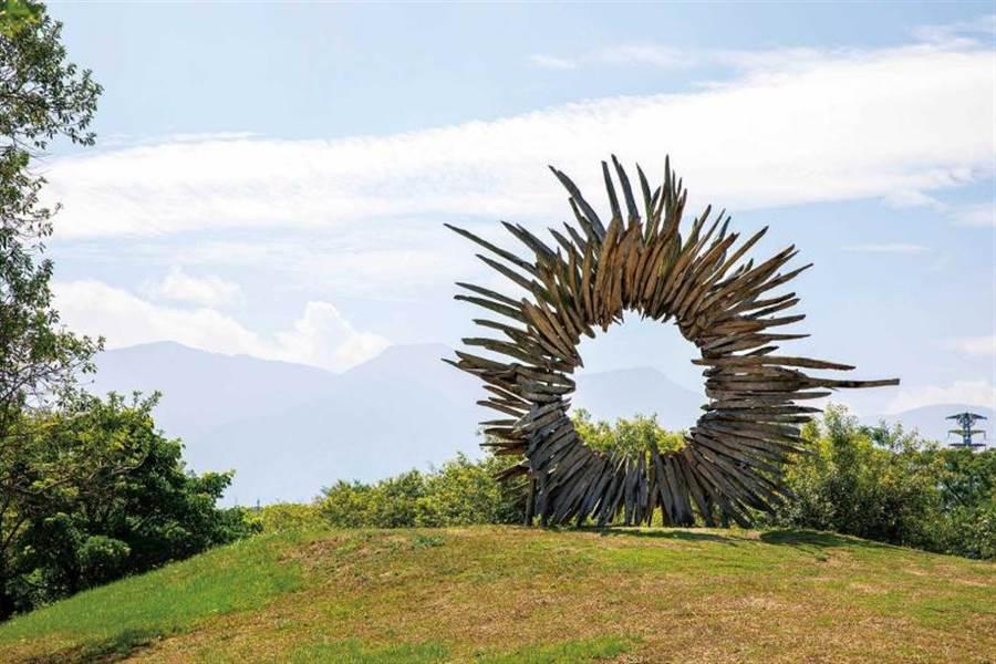 透過太陽花形狀的漂流木藝術品《窗裡窗外》,可看見遠方的大武山。(圖/宋岱融攝)