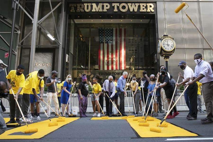 紐約市長白思豪(中,戴橙色口罩者),9日與非裔妻子艾琳(黃上衣白口罩)以及牧師夏普頓,在川普大廈前馬路,漆上黃色的「黑人的命也是命」(BLM)標記。(美聯社)