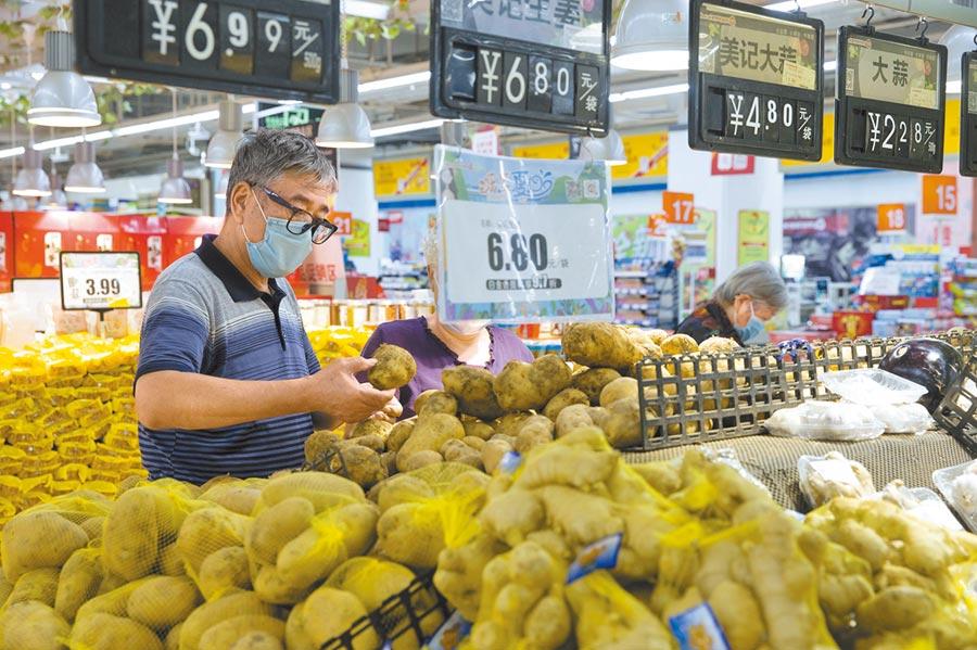 大陸近日水澇嚴重,菜價走揚,圖為民眾9日在太原市一超市選購馬鈴薯。(中新社)