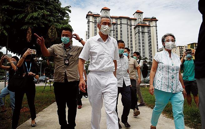 新加坡在疫情下舉行大選。圖為新加坡總理李顯龍(中)和夫人何晶(右)抵達投票所。(路透)