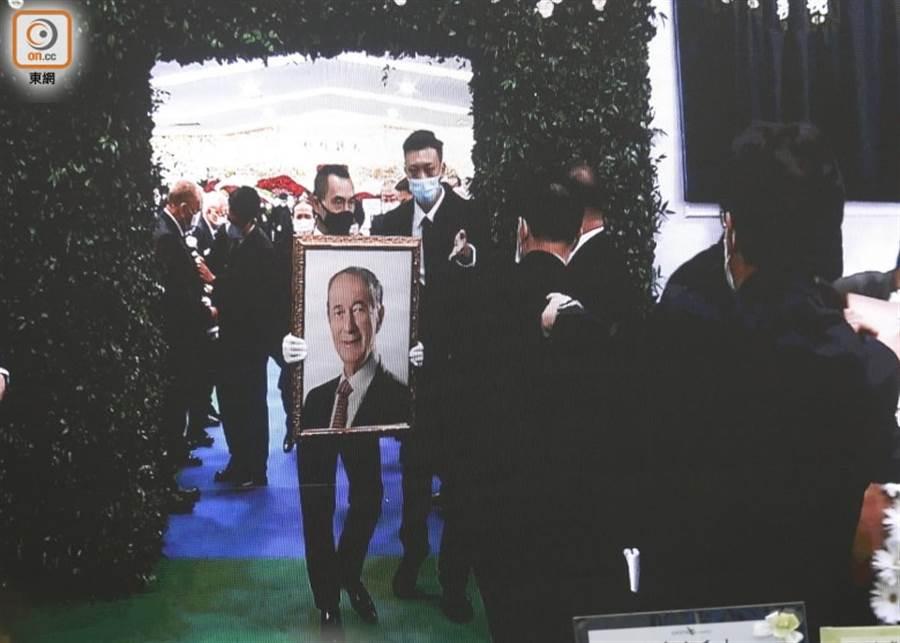 賭王何鴻燊昨日出殯,二房兒子何猷龍手捧父親遺照步出靈堂。(取自東網)
