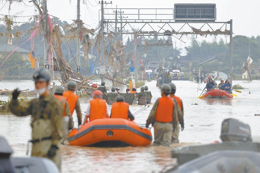 日本自卫队官兵日前在豪雨成灾的熊本县,出动救生艇救援当地一处村庄受困的灾民。(路透)