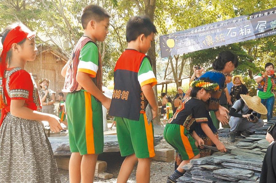 屏東長榮百合國小在校園後山建造1座傳統石板屋,10日舉行建造奠基儀式,部落族人及學生依序拿著小石片堆疊奠基。(潘建志攝)